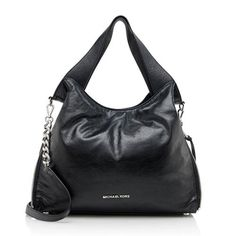 This MICHAEL Michael Kors tote is made from black glazed leather with silver-tone hardware. Details include two flat handles, a detachable shoulder strap, magnetic snap closure, and fully lined interior with four open pockets and one zippered pocket. This versatile design can be carried with the sides open or zipped closed. Carry this style over the shoulder with the handles or detachable shoulder strap.