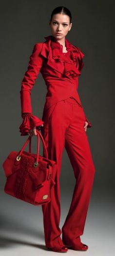 Red blouse with ruffles on collar and cuffs, red tuxedo blazer, red slacks, red wedges, and red bag--Blumarine F/W 12/13