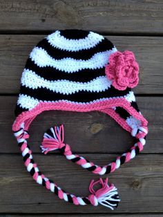 Zebra striped crochet hat with flower, earflaps, and braids, black, white, pink