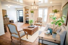 Choosing one wall material for an open concept home unifies connected spaces. Here, designer Joanna Gaines repeated the painted shiplap walls in this home's living room and entryway.