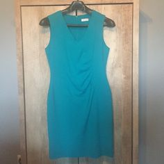 Teal Calvin Klein Dress SZ 12 Very figure flattering, sleeveless, teal Calvin Klein knee length dress. Size 12 Perfect for work with a cardigan or blazer or a dressy night out. Fully lined with invisible zipper. Pleated front to hide any problem areas.  ***just dry cleaned ready to go*** 63% Polyester 33% Rayon 4% Spandex Lining 100% Polyester Calvin Klein Dresses