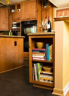 small shelves for cookbooks at the end of kitchen cabinets