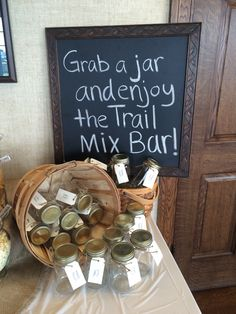 """We used these as party favors! Each mason jar was tagged with """"Happy Trails"""" on one side and """"Thank you for coming to Carter and Coleman's graduation party"""" on the back. Guests could fill their jar with their choice from a variety of trail mix ingredients."""
