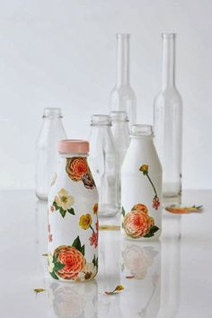 Decoupage! You can paint your wine or any glass bottle in opaque white. When the paint is completely dry, you can select beautiful motifs and decoupage them onto the bottles. You can get a wonderful floral container or vase, or decorated with any other picture you might like.