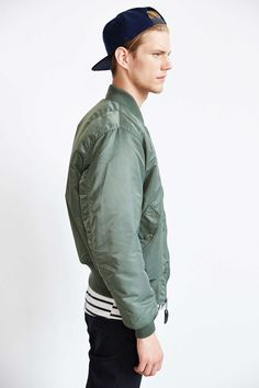 black pant, striped shirt, olive bomber jacket, navy cap