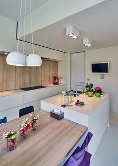 Moderne witte keuken waar de combinatie met hout een warme toets meegeeft.