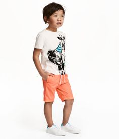 Shorts in a soft, washed woven fabric in cotton. Elasticized drawstring waistband, side pockets, and back pockets.