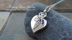 28mm x 19mm silver (stainless steel) cremation urn pendant - 1/4 hand stamped sterling silver disc stamped with an initial - 4mm Swarovski crystal birthstone - Sterling silver angel wing charm - Sterling silver chain This beautiful pendant opens to allow you to place a small
