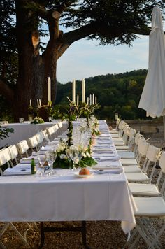A long U shape table set up for an outdoor wedding