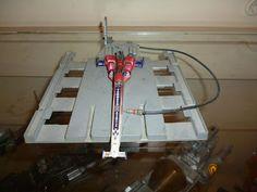 La pista es de una pieza de computadora, junto con otros elementos caseros. La base de la nave es un carro de record de velocidad en tierra que estaba dañado. Los propulsores son de un robot transformable desechado.