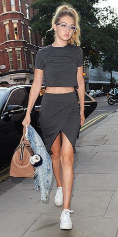 Gigi Hadid in a gray crop top and skirt, sneakers, and glasses