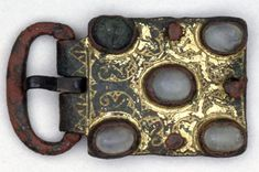 12th cent Belt-buckle found in England; copper alloy; gilt; back plate missing; rectangular with oblong loop and short painted tongue(now bent); plate decorated with raised settings for five crystals: four surviving: two cut en cabochon; between these settings the plate is engraved with stylised half-palmettes; zigzag on hinge. -British Musuem