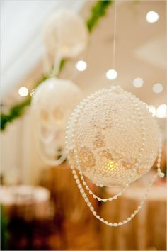 The lanterns are made by overlapping lace doilies on an inflated balloon and brushing fabric stiffener (or wallpaper glue, or even white glue) onto the doilies. Be sure to cover it completely so that the whole thing hardens and you aren't left with limp spots. Let the doilies dry overnight to ensure that they are completely dry. The last step is to pop the balloon and pull it out of the opening. The lanterns can be hung with a ribbon or fishing line draped with strands of beads.