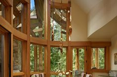 Beautiful curving windows beside a glass top kitchen table. Discovered on www.Porch.com