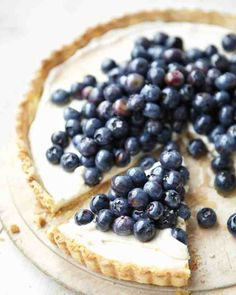 Blueberry-Ricotta Tart Recipe - Under a beautiful crown of blueberries is a luscious, lightly sweetened ricotta tart. It's a delightful, healthy dessert with a crust made with whole wheat flour, all-purpose flour, and ground almonds.