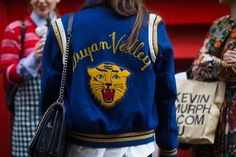 A vintage varsity jacket is paired with a white button-down and a black chain shoulder bag