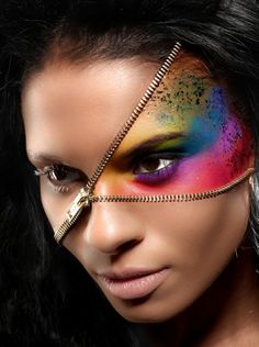 Zipper themed makeup for Halloween. This look uses a real zipper fastened around your head while creating a rainbow themed half face paint design topped with glitter for effect.