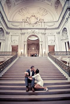 A couple sits on the grand staircase after their San Francisco City Hall Wedding. Photographed by Rebecca Wilkowski Photography. www.RebeccaWilkowski.com