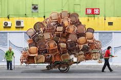 """In """"Totems,"""" antlike workers balance often-bizarre wares, such as flowers, furniture, balloons — and even tires — on their bikes and carts as they weave precariously through Shanghai's streets. And photographer Alain Delorme captures it all.http://slate.me/XF92BZ"""