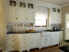 This quaint cottage kitchen features antique white Shaker cabinets, black countertops and a white subway tile backsplash. A white apron-front sink adds a farmhouse-feel to the space.