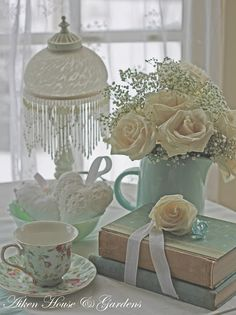vintage books, cup of tea, an aqua pitcher of cream roses and a lovely lamp dripping with beaded fringe  - crochet hearts - All is shabby chic style!