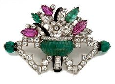 An art deco diamond, gem-set and enamel brooch, circa 1925 centering a carved emerald vase containing a floral motif of carved emerald and ruby leaves, accented by an openwork geometric base of old European and baguette-cut diamonds; estimated total diamond weight: 2.75 carats; mounted in platinum.