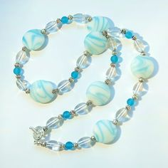 Lampworked lentils with white and blue swirls, aqua beach glass and clear Czech glass beads. Sterling silver-plated toggle. Approximate fastened length, 20 inches.