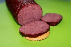 Slice of Deer summer sausage on a cracker on a lime green cutting board sausage recipe Homemade Venison Summer Sausage Venison Sausage Recipes, Homemade Sausage Recipes, Jerky Recipes, Venison Summer Sausage Recipe Smoked, Homemade Venison Breakfast Sausage Recipe, Venison Meat Stick Recipe, Smoked Sausages, Homemade Jerky, Snacks Homemade
