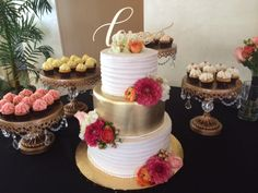 Gorgeous 6x8x10 cake with a hand painted gold center tier. And mini cupcakes on our gold chandelier cake stands for rent!