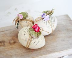 pretty eggs: painted wood eggs, bits of sheet music/book pages, twine and mini flowers