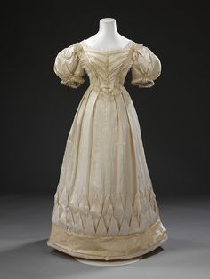 1828 - London, Britain -- White silk wedding dress with detachable sleeves _(removed in photo),_ trimmed with pleated bands of gold-coloured silk satin, white silk satin ribbon, hand-made silk blonde lace, and lined with cotton. __ Has a matching pelerine that is silk, partially lined with silk. __ Wedding dress' hem's circumference is 276 cm.