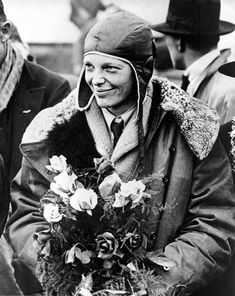 """American aviatrix Amelia Earhart poses with flowers as she arrives in Southampton, England, after her transatlantic flight on the """"Friendship"""" from Burry Point, Wales, on June 26, 1928. The tri-motor """"Friendship"""" was piloted by two men as Earhart served as the commander, making her the first woman passenger to fly across the Atlantic"""