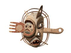 This ceremonial dance mask apparently depicts the kind of powerful tunraaq spirit that lived in the moon and controlled the availability of sea mammals. The spirit's hand is shown with no thumb and a hole in its palm, symbolizing the community's desire that it not hold on to all of the animals, allowing some to return for spring hunting. The face of a seal emerges from the left side of the face and other mask appendages include the bow of a kayak and a fin, possibly of a whale. Magemut