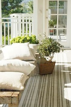 Nice Hollywood Hills porch with white railing, a reclaimed wood bench and striped runner in tan and off white.  Cute overlooking the garden yard. http://cococozy.com