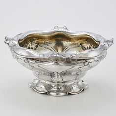 "GORHAM MARTELE SILVER CENTER BOWL; Softly billowed form with undulating everted rim, conforming pedestal foot, decorated throughout with broad blossom and whiplash straps, gilt interior, ca. 1900; Type III mark, scratch mark 15EXE; 11 5/8"" x 10 1/2"" x 5 1/2""; 54.7 OT; Note: Similar decoration found on ES Vase 1/29/1901, apparently shown at Panama Pacific International Exposition, 1915. Reference ""Martel_©, Gorham""s Art Nouveau Silver"", L. J. Pristo, Ph.D., p.62. - Price Estimate: $8000…"
