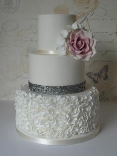 Elegant while ruffled wedding cake with silver and floral accents