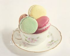 Pretty French macarons in a vintage teacup. Pistachio, raspberry and lemon are…