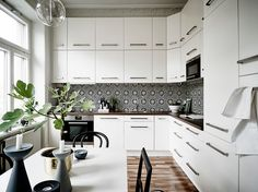 Love the detail in the tile backsplash in this white kitchen