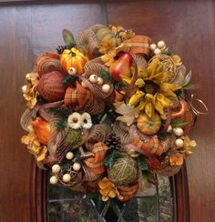 This 24 inch deluxe mesh wreath has a wooden and moss owl in it surrounded with lots of decorative wooden balls, pumpkins, pears, sunflower, berries and pine cones with decorative fall plaid ribbon and roping all through the wreath.