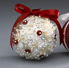 """Red & White Keepsake Button Ornament: You'll want to display this heirloom ornament year-round. Just randomly pin the pretty buttons in place with pearl head pins to a 4"""" styrofoam ball. Top with a red ribbon bow to hang."""