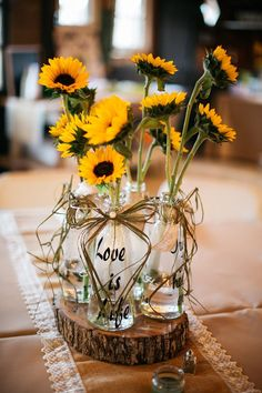 DIY simple sunflower bouquets on a wooden round base at Hadley and Kodi's Vintage Rustic Georgia Wedding at Fritz Farm. TR Photography