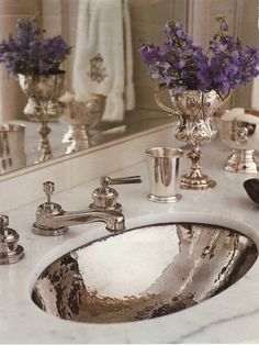 Carrera marble vanity with a hammered silver sink, silver faucet and accessories, trophy with flowers - Circa Interiors & Antiques - Jane Schwab, Designer - Photo by Michael Parteno