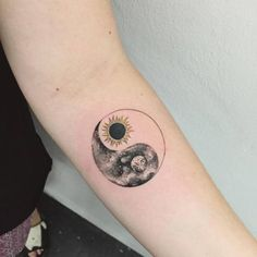 Sun-moon Yin Yang tattoo on the forearm.
