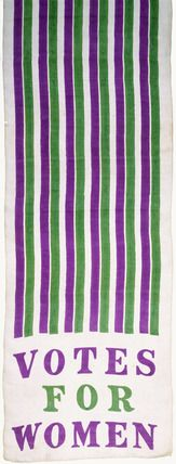 1908, UK: Suffragette motor scarf of white Japanese silk with green and purple stripes, the WSPU colours. The 'Votes for Women' slogan is printed on the borders. The W.S.P.U. encouraged members to wear purple, white and green at all times, particularly when attending large demonstrations.