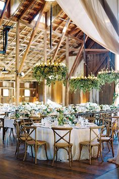 Kate Holt of Flower Wild hung masses of vines and ethereal panels of fabric for a barn reception. Photo by Jose Villa