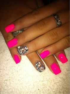 Bright pink nails with one glitter nail. Lots of bling!