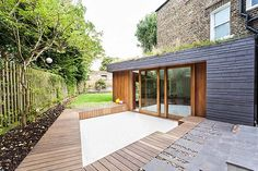 Kitchen: The exterior of the extension is clad in timber and slate clad and the green roof is seeded with meadow flowers