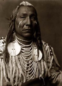 Here for your perusal is a collectible photograph of Red Wing, a Crow Indian Brave. It was created in 1908 in Montana by Edward S. Curtis.    The photograph illustrates this Crow Brave with streaks of white paint on his cheeks and hair, and a beaded buckskin shirt trimmed with ermine tails or white rabbit fur.