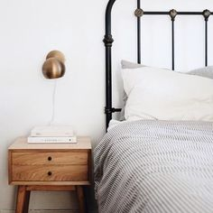 I love the pairing of a black metal bed with grey ticking stripe and a mid-century modern nightstand.