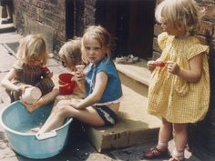 Four young girls play out on the pavement in Hulme, Manchester. One girl in a yellow dress has a red ice lolly and one girl sitting on the step to her house holds an ice cream cone. Summer Fun For Kids, Cool Kids, Shirley Baker, 1960s Britain, Fun Live, Working Class, 1960s Fashion, Documentary Photography, First Girl